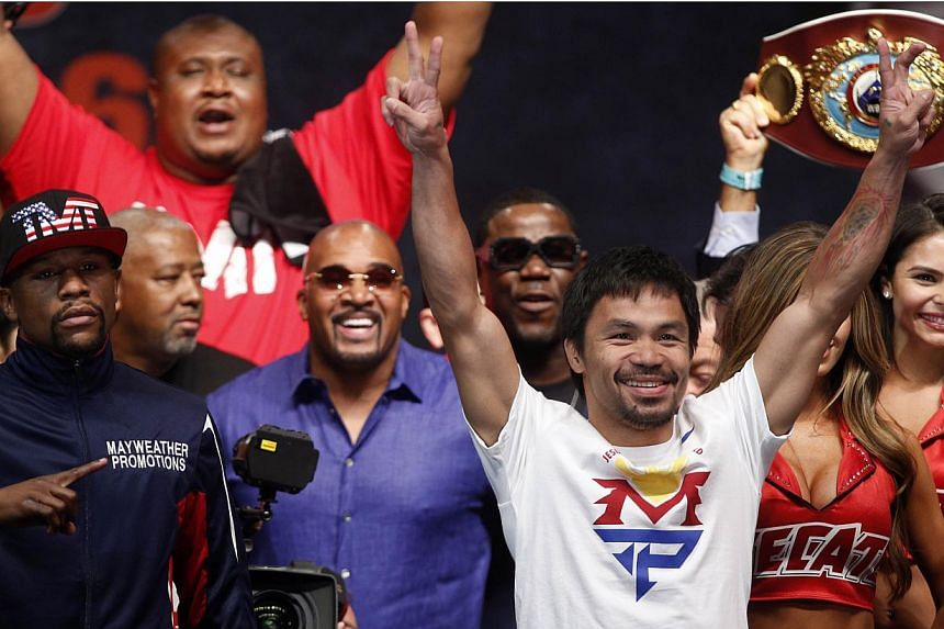 "Floyd Mayweather (left) and Manny Pacquiao (right) gesturing following their weigh-in on May 1, 2015, in Las Vegas, one day before their ""Fight of the Century"" on May 2 at the MGM Grand Garden Arena. -- PHOTO: AFP"