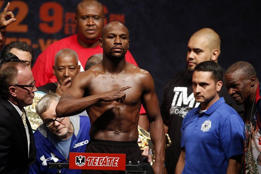 """Floyd Mayweather gesturing while standing on the scale at his weigh-in on May 1, 2015, in Las Vegas, one day before their """"Fight of the Century"""" on May 2 at the MGM Grand Garden Arena. -- PHOTO: AFP"""
