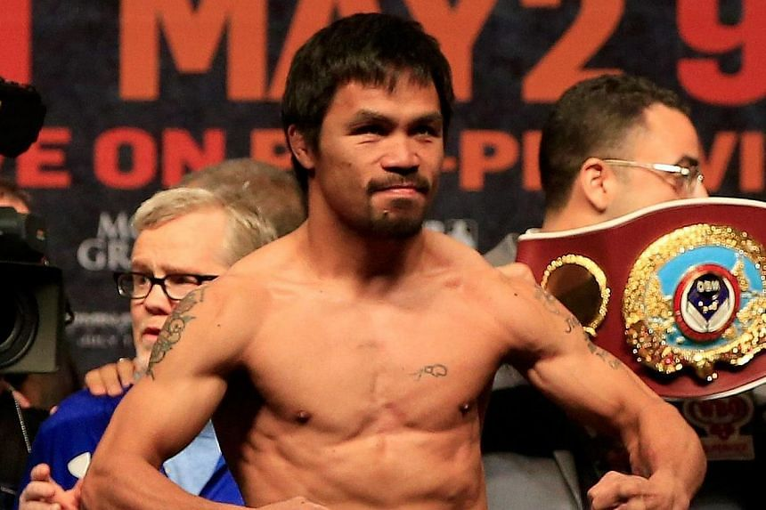 Manny Pacquiao posing on the scale during his official weigh-in on May 1, 2015, at MGM Grand Garden Arena in Las Vegas. Pacquiao will face Floyd Mayweather Jr. in a welterweight unification bout on May 2, 2015, in Las Vegas. -- PHOTO: AFP
