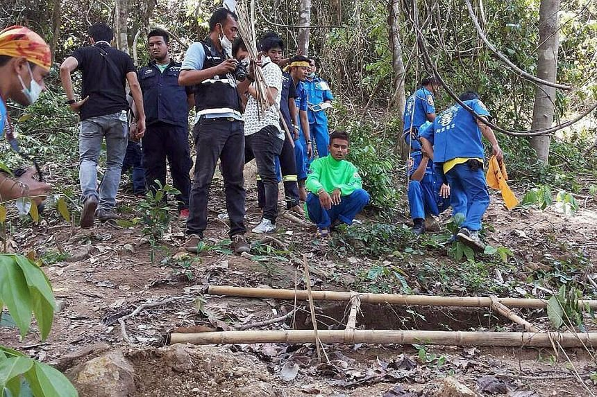 Rescue workers and forensic officials inspecting the site of a mass grave uncovered at an abandoned jungle camp in the Sadao district of Thailand's southern Songkhla province on May 1, 2015. -- PHOTO: AFP