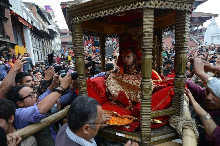 """Nepal's Living Goddess the """"Kumari Devi"""" is carried by worshippers during a procession on the third day of the Seto Machindranath chariot festival in Kathmandu on March 29, 2015. --PHOTO: AFP"""