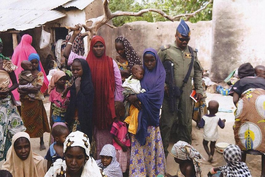 A member of the Nigerian Army standing next to a group of women and children rescued in an operation against the Islamist group Boko Haram in the Sambisa Forest, Borno state, on April 30, 2015. -- PHOTO: AFP