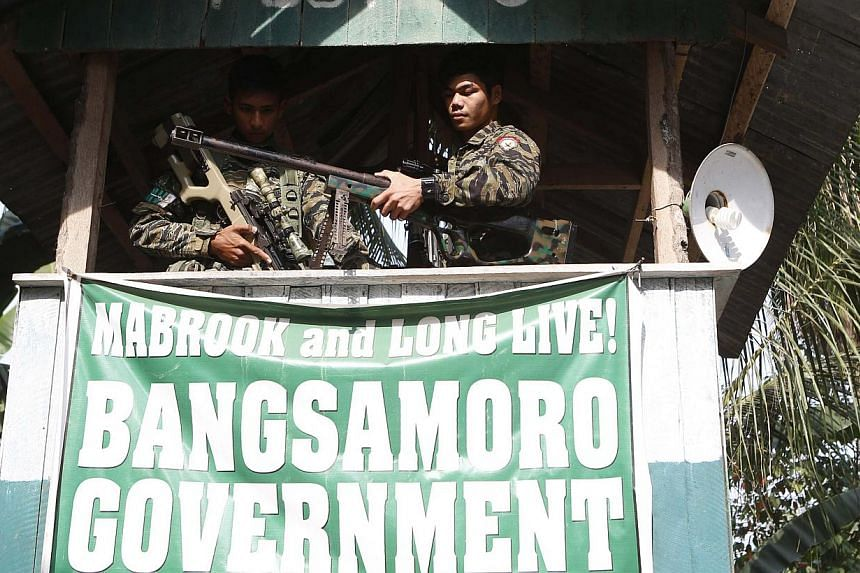 Moro National Liberation Front (MILF) rebels take up position at a guard post at Camp Darapanan rebel base in Maguindanao province, in the southern Philippines, on March 12, 2015. -- PHOTO: REUTERS