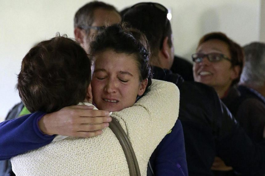A relative embracing a Spaniard evacuated from Nepal at an air base outside of Madrid on April 28, 2015. 1,000 European Union citizens are still unaccounted for in Nepal, diplomats said, almost a week after a massive earthquake that has claimed more