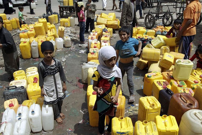 Yemeni children wait to fill their jerrycans with water from a public tap amid an acute shortage of water supply to houses in the capital Sanaa, on April 26, 2015. -- PHOTO: AFP