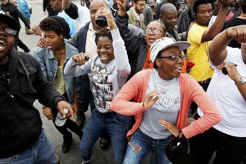 People celebrate as they gather in the streets of Baltimore, Maryland, on May 1, 2015, following the decision to charge six Baltimore police officers - including one with murder - in the death of Freddie Gray, a black man who was arrested and suffere
