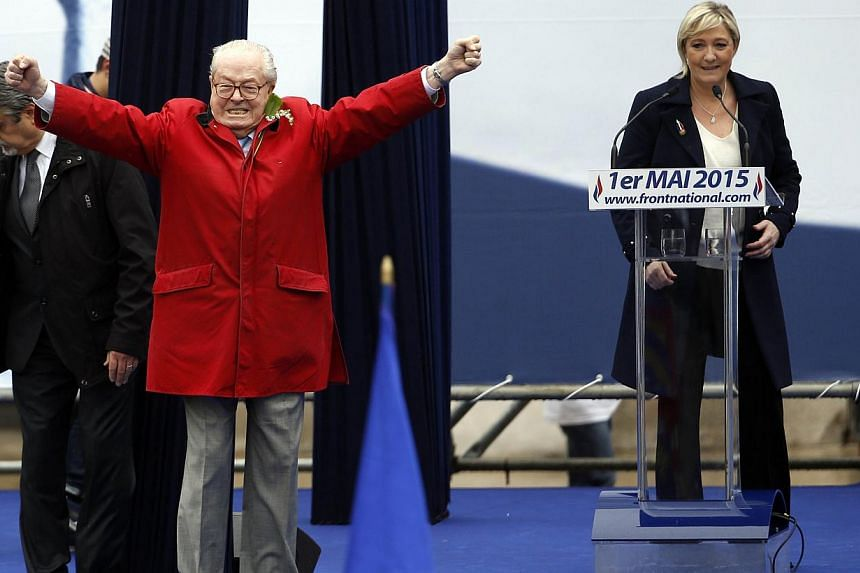 National Front founder and honorary president Jean-Marie Le Pen gestures on stage as his daughter, party leader Marine Le Pen, looks on, during a May Day rally in Paris on May 1, 2015. Following a recent feud with his daughter, Le Pen strode uninvite