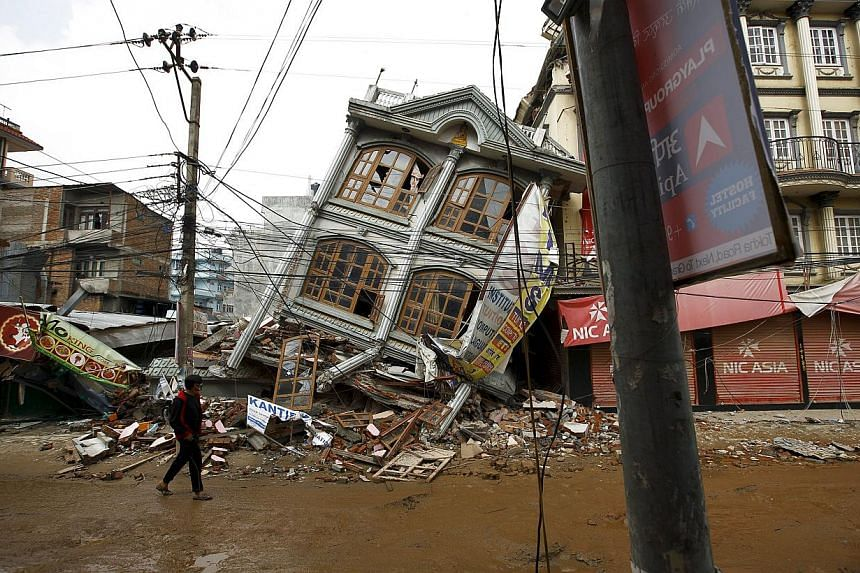 A man walks along the street near a collapsed house following Saturday's earthquake in Kathmandu, Nepal May 1, 2015. US military aircraft, heavy equipment and air traffic controllers will start arriving in Nepal from Saturday as part of a US relief o