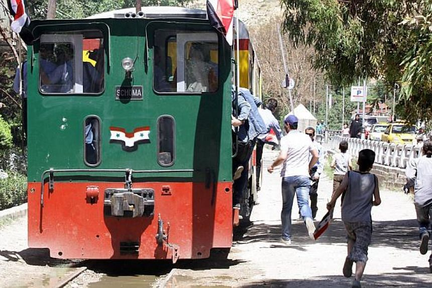Syrians ride the tourist train flying Syrian flags in Damascus, following the re-opening ceremony of the rail route between two neighbourhoods in the Syrian capital, Rabwa and Dumar, on May 1, 2015. -- PHOTO: AFP