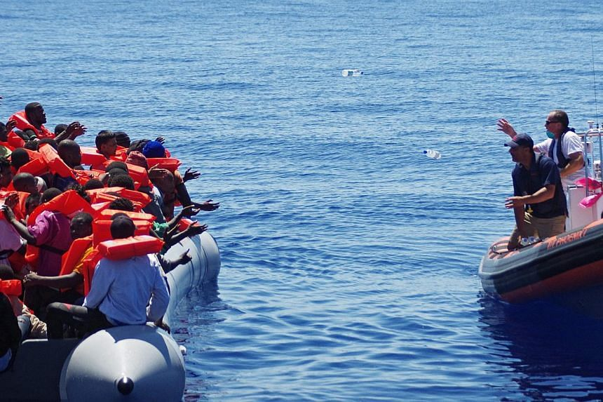 A handout picture made available on May 2, 2015 of Migrant Offshore Aid Station (MOAS) employees throwing bottles of water from a dinghy of the ship 'Phoenix' to refugees in a rubber raft off Malta, on August 30, 2014. -- PHOTO: EPA