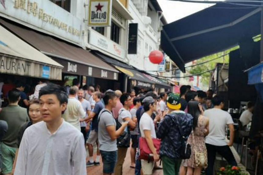 The slight drizzle fails to rain on the parade of these boxing fans in Boat Quay. -- PHOTO: TWITTER