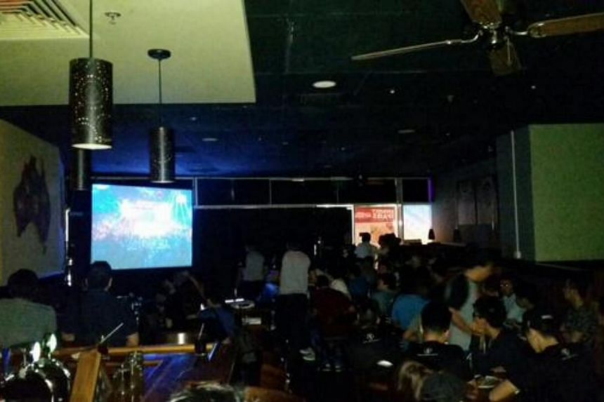 A crowd of about 200 gathering in front of a screen in Outback Steakhouse at Millenia Walk. -- PHOTO: TWITTER
