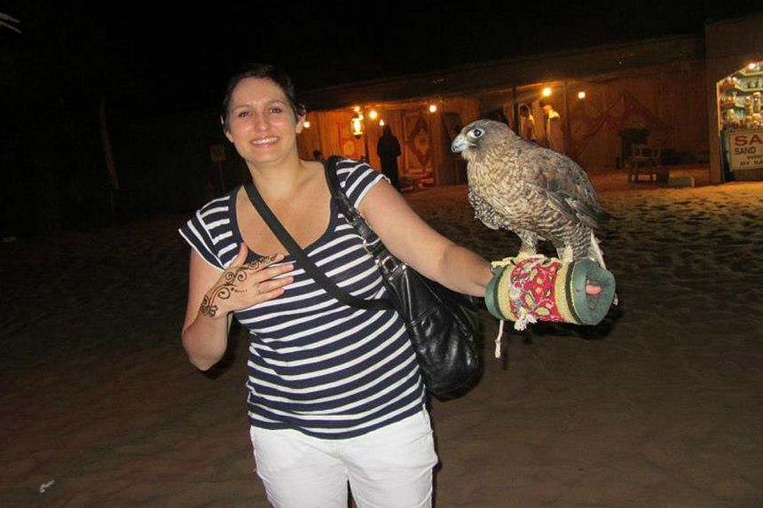 Ms Katherine Cole extending a hand to a bird of prey at a falcon show in the Arabian Desert.