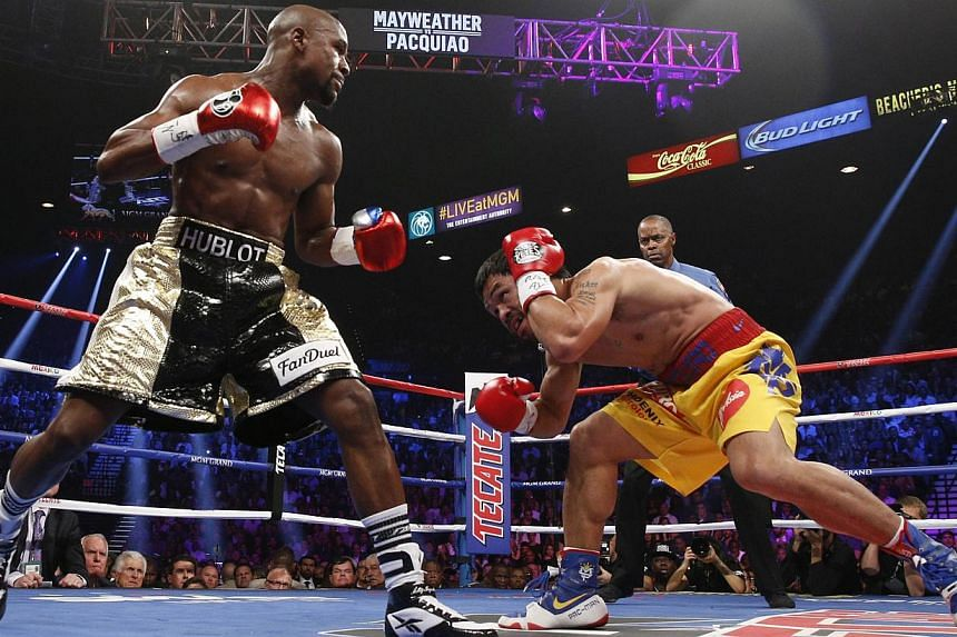 Floyd Mayweather Jr. and Manny Pacquiao (right) fight in a welterweight unification bout on May 2, 2015 at the MGM Grand Garden Arena in Las Vegas, Nevada. -- PHOTO: AFP