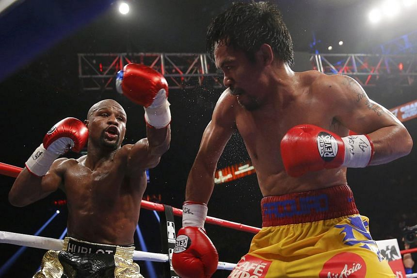 Floyd Mayweather, Jr. of the U.S. (left) and Manny Pacquiao of the Philippines fight in the tenth round during their welterweight WBO, WBC and WBA (Super) title fight in Las Vegas, Nevada, on May 2, 2015. -- PHOTO: REUTERS
