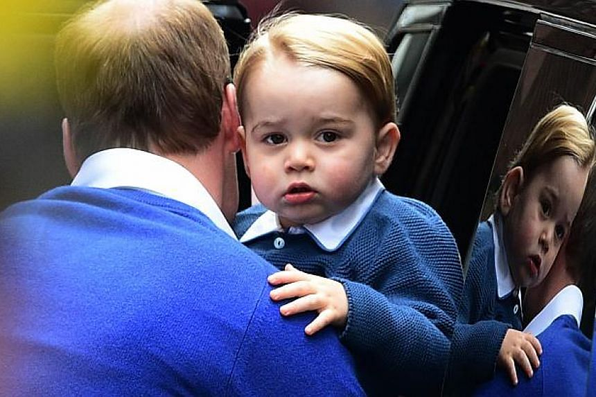Britain's Prince William helps his son Prince George out of a car as they return to the Lindo Wing at St Mary's Hospital in central London, on May 2, 2015, where his wife Catherine gave birth to their second child, a baby girl, earlier in the day. --