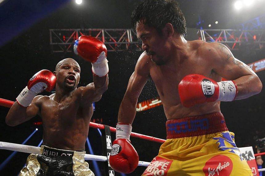 Floyd Mayweather of the US (left) and Manny Pacquiao of the Philippines fight in the tenth round during their welterweight WBO, WBC and WBA (Super) title fight in Las Vegas, Nevada, on May 2, 2015. -- PHOTO: REUTERS