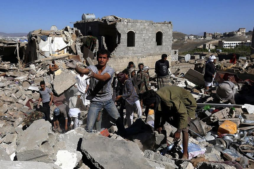 Yemenis inspecting houses which were allegedly destroyed by an air strike of the Saudi-led coalition targeting Houthi rebels' nearby positions in Sana'a, Yemen, on May 1, 2015. Rights group Human Rights Watch accused the Saudi-led coalition of us
