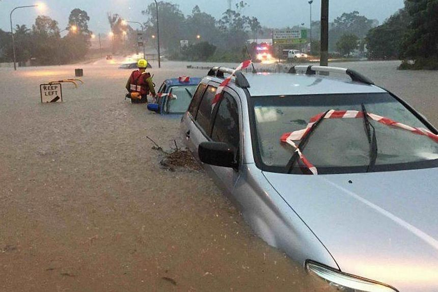 Swift water operators assessing vehicles submerged in floodwaters in Brisbane, Australia, on May 1, 2015.The death toll from heavy rains that inundated Australia's east coast has climbed to six, as flood warnings continued Sunday following a se