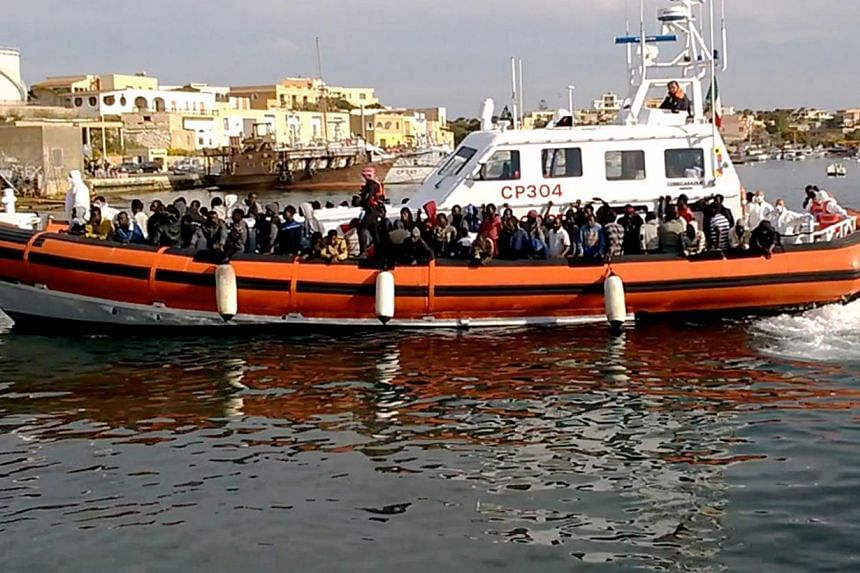 An Italian coast guard ship transporting migrants arriving in Lampedusa harbour on May 1, 2015.Italy's coast guard attempted to rescue more migrants in the Mediterranean on Sunday, May 3, after nearly 3,700 were picked up trying to reach Europe