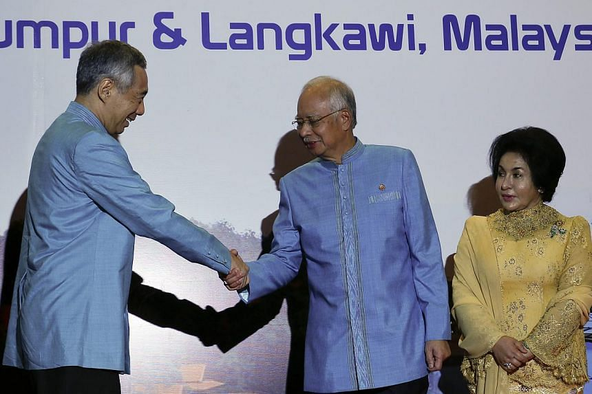 Singapore's Prime Minister Lee Hsien Loong (left) shake hands with Malaysian Prime Minister Najib Razak (centre) during the 26th Asean Summit in Kuala Lumpur on April 26, 2015. -- PHOTO: EPA