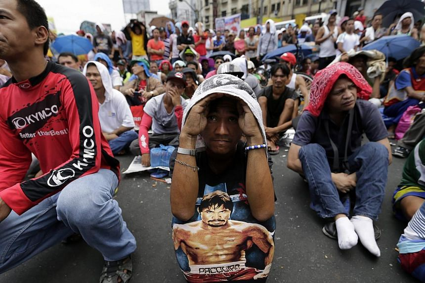 Filipino spectators react as they watch a broadcast from Las Vegas, USA, of a boxing match between Filipino boxer Manny 'Pacman' Pacquiao and US boxer Floyd Mayweather Junior for the WBC welterweight title, outside a church at a street in Manila, Phi