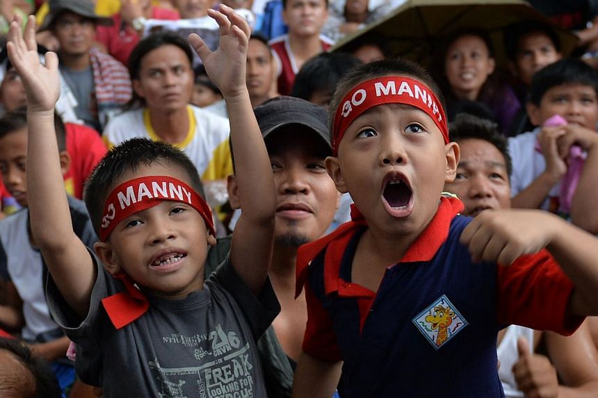 Fans watch a live telecast of the welterweight unification bout between Filipino boxer Manny Pacquiao and US boxer Floyd Mayweather, at a plaza in Marikina City suburban Manila on May 3, 2015. -- PHOTO: AFP
