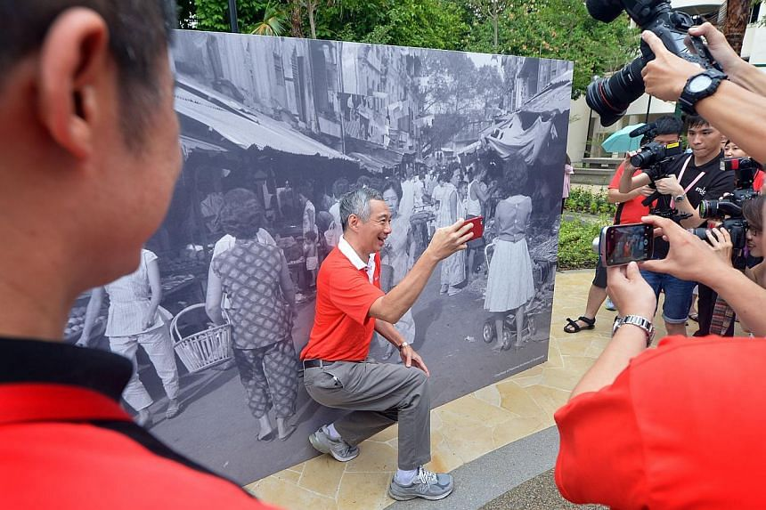 Prime Minister Lee Hsien Loong takes a selfie in front of a mural at the SG50 Carnival by Ang Mo Kio-Hougang Grassroots Organisations at Hougang Avenue 8 on May 3, 2015. -- ST PHOTO: ALPHONSUS CHERN
