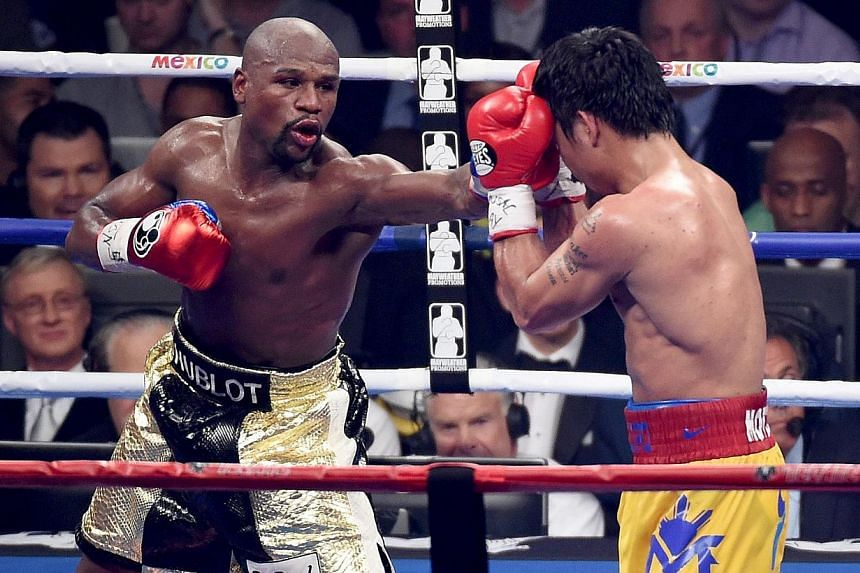 Floyd Mayweather Jr. throws a left at Manny Pacquiao during their welterweight unification championship bout on May 2, 2015 at MGM Grand Garden Arena in Las Vegas, Nevada. -- PHOTO: AFP