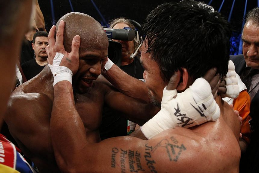 Floyd Mayweather Jr. hugs Manny Pacquiao after defeating Pacquiao in their welterweight unification bout on May 2, 2015 at the MGM Grand Garden Arena in Las Vegas, Nevada.-- PHOTO: AFP