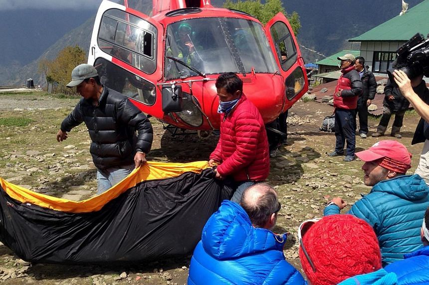 A body bag containing the body of a climber is carried from a helicopter in the Himalayan tourist town of Lukla April 29, 2015.Police have found more than 50 bodies, including those of six foreigners, in Nepal's popular Langtang trekking region