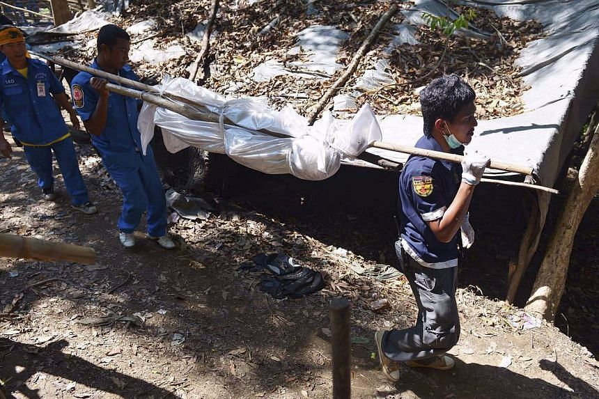 Twenty-six bodies exhumed from a mass grave near a suspected human trafficking camp in southern Thailand do not bear signs of violent death, the police said on Sunday, following initial forensic examinations at the site. -- PHOTO: REUTERS