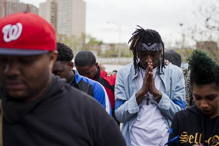 Protesters pray outside the Baltimore Police Central Booking and Intake Centre for prisoners in Baltimore, Maryland on May 1, 2015. The city of Baltimore was on Sunday, May 3, to observe a day of prayer two weeks after a 25-year-old black man di