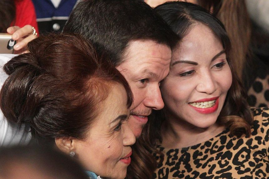 Actor Mark Wahlberg (centre) taking a picture with Dionisia Pacquiao (left), better known as Mommy D, at her son Manny's fight against American boxer Floyd Mayweather Jr at at the MGM Grand Garden Arena in Las Vegas, Nevada, on May , 2015. -- PHOTO: