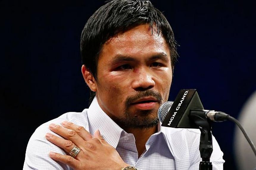 Manny Pacquiao points to his right shoulder during the post-fight news conference after losing to Floyd Mayweather Jr. in their welterweight unification championship bout on May 2, 2015 at MGM Grand Garden Arena in Las Vegas, Nevada.-- PHOTO: R