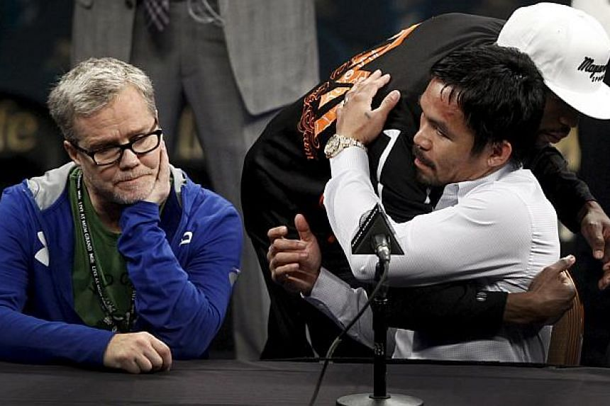 WBC/WBA/WBO welterweight champion Floyd Mayweather Jr. of the U.S. embraces Manny Pacquiao at a post-fight news conference at the MGM Grand Arena in Las Vegas, Nevada on May 2, 2015. Pacquiao's trainer Freddie Roach is seen on the left. Mayweather to