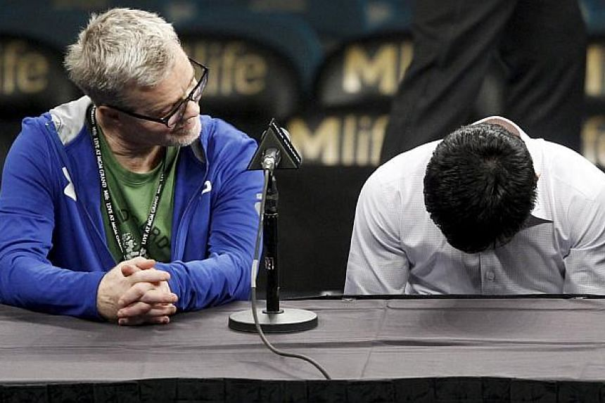 Manny Pacquiao (right) of the Philippines hangs his head as his trainer Freddie Roach looks on during a post-fight news conference after losing to Floyd Mayweather Jr. of the U.S. at the MGM Grand Arena in Las Vegas, Nevada on May 2, 2015. Mayweather