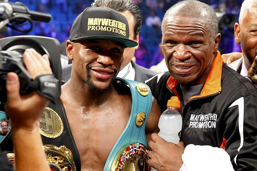 Floyd Mayweather, Jr. of the U.S. and his trainer Rafael Garcia (right) pose for a picture after Mayweather defeated Manny Pacquiao of the Philippines in their welterweight WBO, WBC and WBA (Super) title fight in Las Vegas, Nevada, on May 2, 2015. --