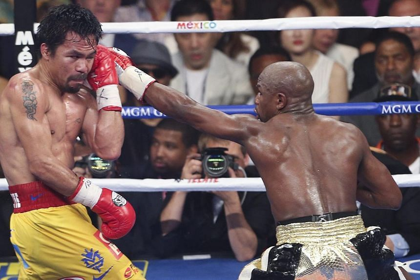 Floyd Mayweather Jr. (right) in action against Manny Pacquiao (left) during their welterweight unification championship boxing fight at the MGM Grand Garden Arena in Las Vegas, Nevada, USA, on May 2, 2015.-- PHOTO: EPA