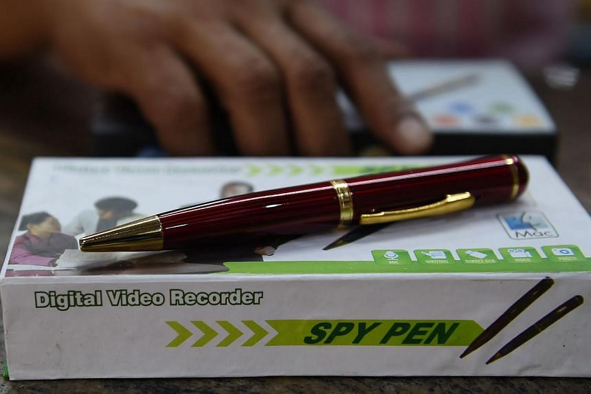 """In this photograph taken on April 17, 2015, an Indian shopkeeper presents a 'spy pen' - a pen with a camera fitted - at a store in New Delhi. Tiny bluetooth earpieces, """"spy bras"""" and hidden camera glasses: these are just some of the high-tech gadgets"""
