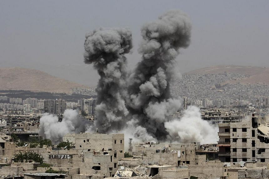 Smoke billows following air strikes by regime forces in the rebel-held area of Ain Tarma, east of the capital Damascus, on April 29, 2015. -- PHOTO: AFP