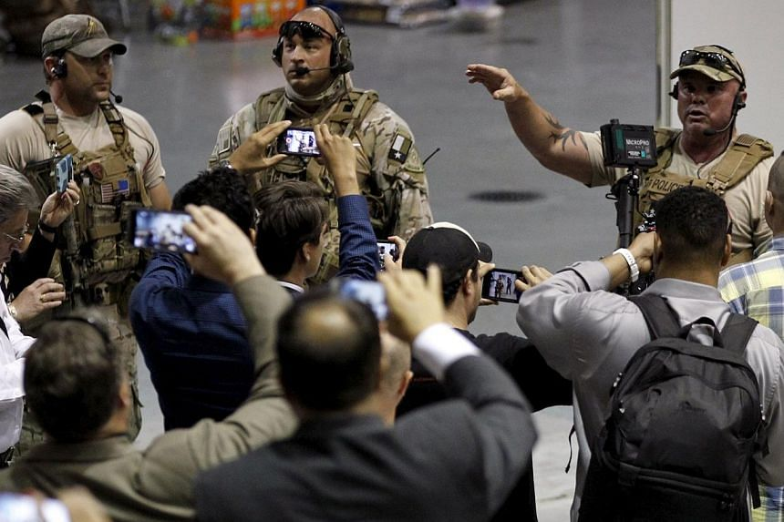 Police officers address attendees at the Muhammad Art Exhibit and Contest.Two gunmen opened fire at an anti-Islam art show featuring depictions of the Prophet Mohammad in Garland, Texas, near Dallas on Sunday.-- PHOTO: REUTERS