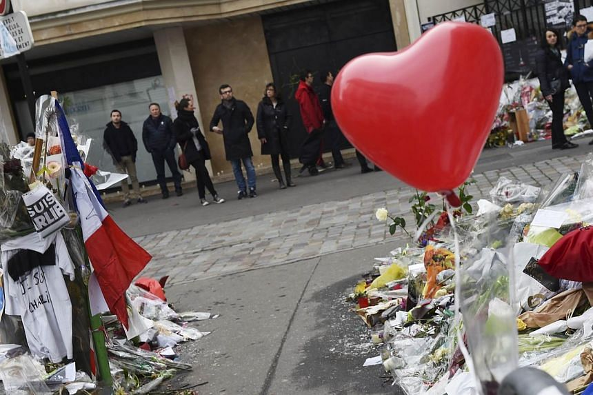 People paying homage outside the headquarters of French satirical weekly Charlie Hebdo in Paris on Feb 15, 2015. -- PHOTO: AFP