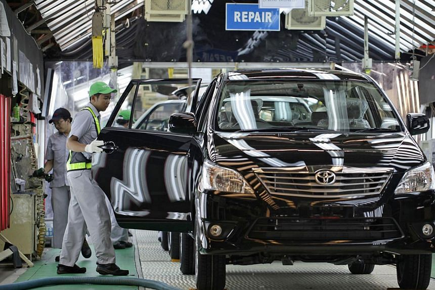 A worker makes a final check on a Toyota Motor Corp. Kijang Innova minivan on the production line of PT. Toyota Motor Manufacturing Indonesia's (TMMIN) Karawang plant in Karawang, West Java, Indonesia. -- PHOTO: BLOOMBERG