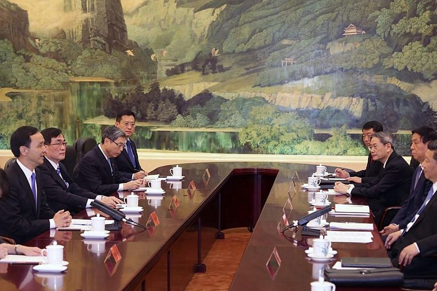 A handout photo released by Taiwan's ruling party the Chinese Nationalist Party (Kuomintang or KMT), shows Chinese President Xi Jinping (right), in his capacity as secretary-general of the Chinese Communist Party, meeting with KMT Chairman Eric Chu (