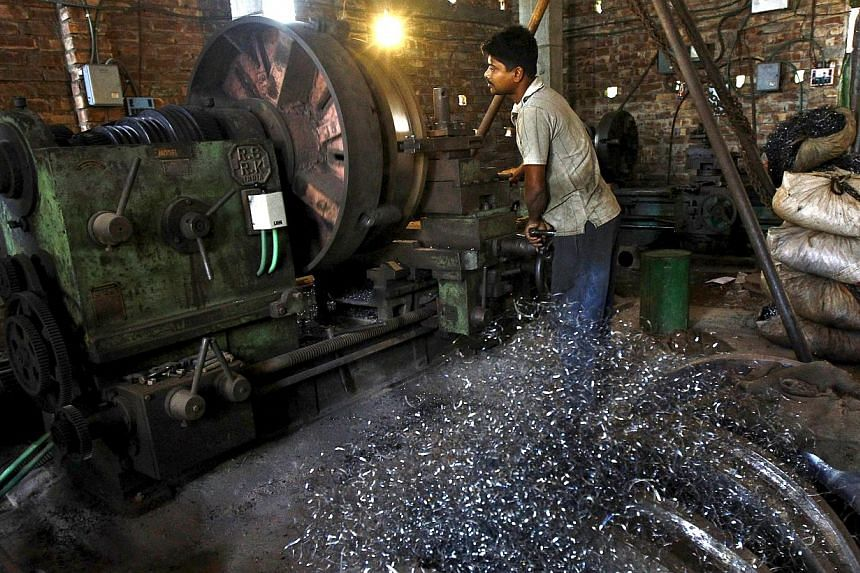 A worker makes gear parts for cranes inside a workshop on the outskirts of Kolkata on April 2, 2015. Indian manufacturing growth eased in April as domestic demand softened, despite factories cutting prices for the first time in nearly two years, a bu