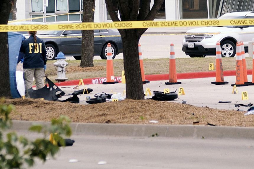 An FBI agent views debris of a car blown up by police as a precaution, near the Curtis Culwell Center on May 4, 2015 in Garland,Texas. Police in Texas shot dead two gunmen outside a Prophet Mohammed cartoon contest put on by a group that has a histor