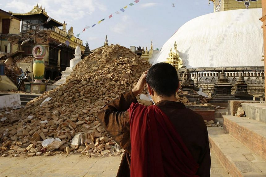 A monk inspects the damage at Nepalese heritage site Syambhunaath Stupa, also known as monkey temple, after a powerful earthquake struck Nepal, in Kathmandu, Nepal, on April 26, 2015. -- PHOTO: EPA