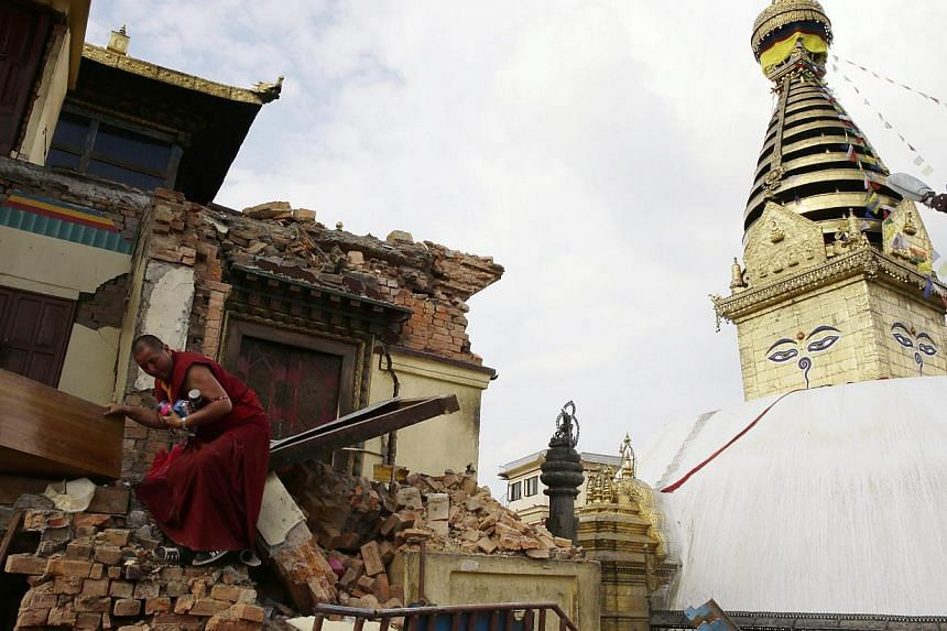 A monk salvages belongings from the rubble at Nepalese heritage site Syambhunaath Stupa, also known as monkey temple, after a powerful earthquake struck Nepal, in Kathmandu, Nepal, on April 26, 2015. -- PHOTO: EPA