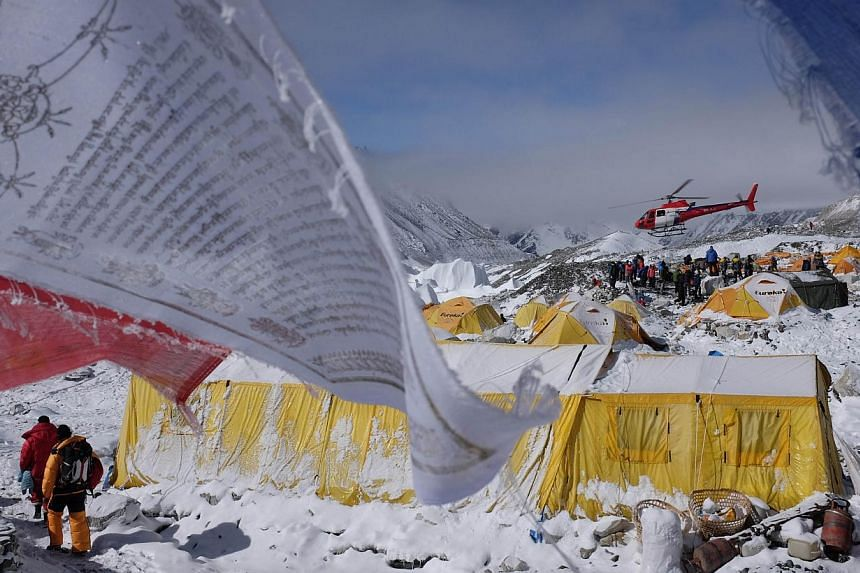 This April 26, 2015, photo shows Buddhist prayer flags fluttering in the wind near tents as a rescue helicopter takes off from Everest Base Camp, after an earthquake-triggered avalanche crashed through parts of the base camp, killing scores of people